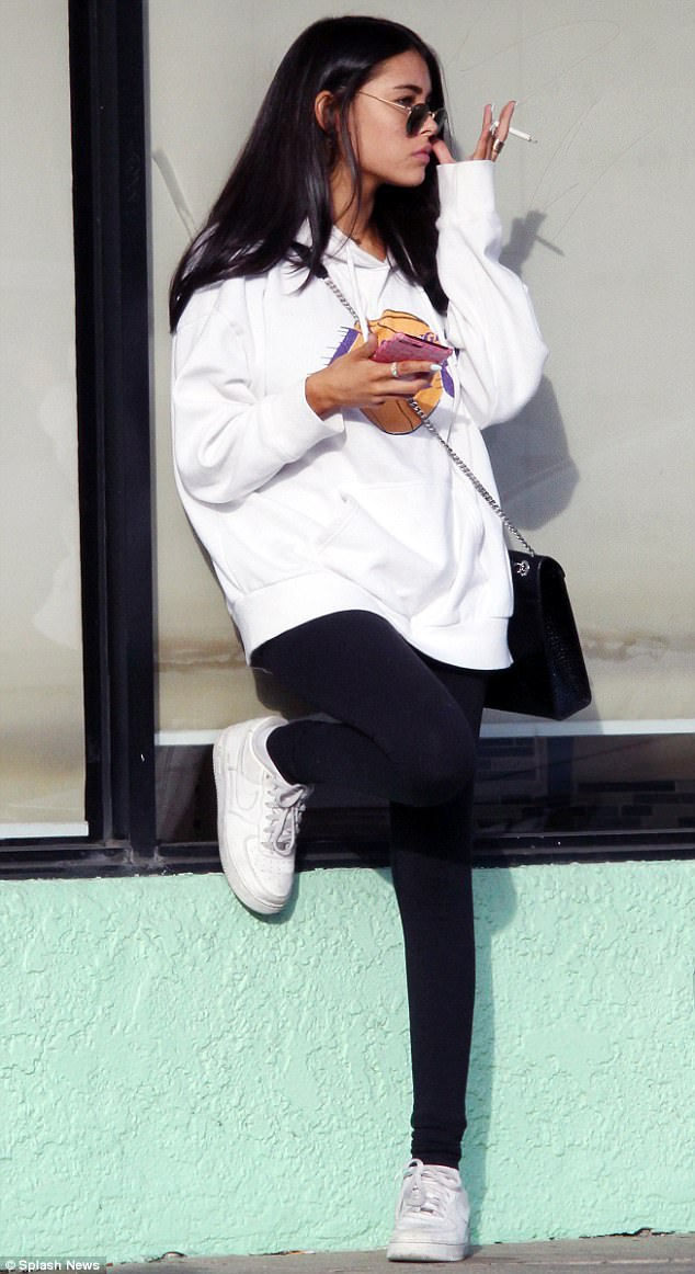 Relaxed: The starlet was pictured with a cigarette in hand as hid her enviably slender figure under an oversized hooded jumper while leaned against a window