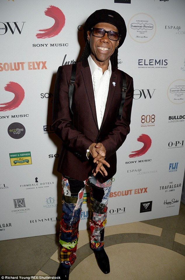 Colourful as always: Nile Rodgers showed off his quirky sense of style in patchwork trousers and burgundy blazer, fit with a crisp white ruffled shirt.