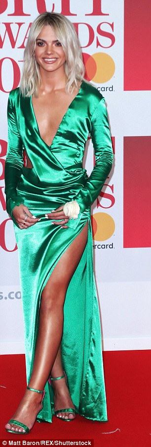 Daring: Rocking up in a metallic green dress, Louisa turned heads in the gown, which featured a variety of intricate cut-outs, teasing her torso and her lean pins