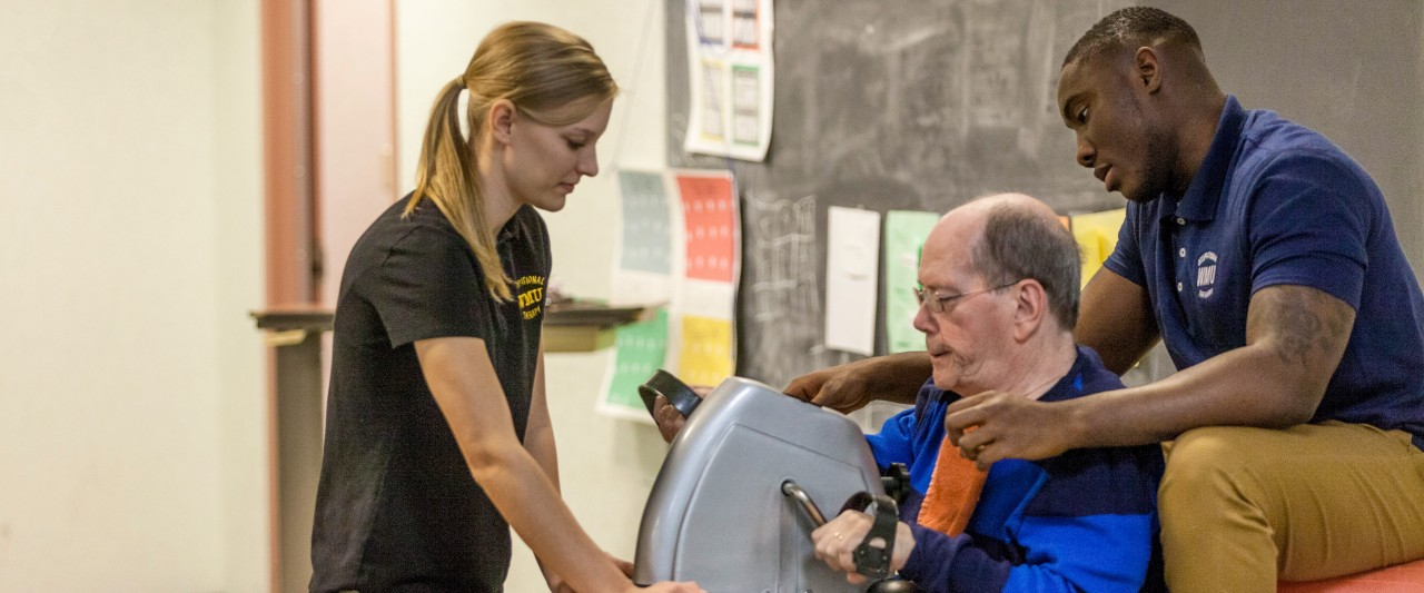 Two student clinicians help an older patient perform occupational therapy exercises.