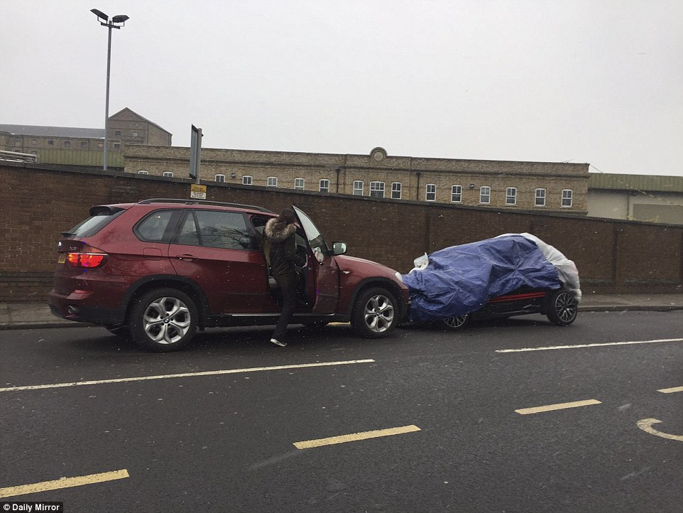 A woman is seen opening the door of one of the cars involved in the crash, today. McPartlin's car has been covered up by police