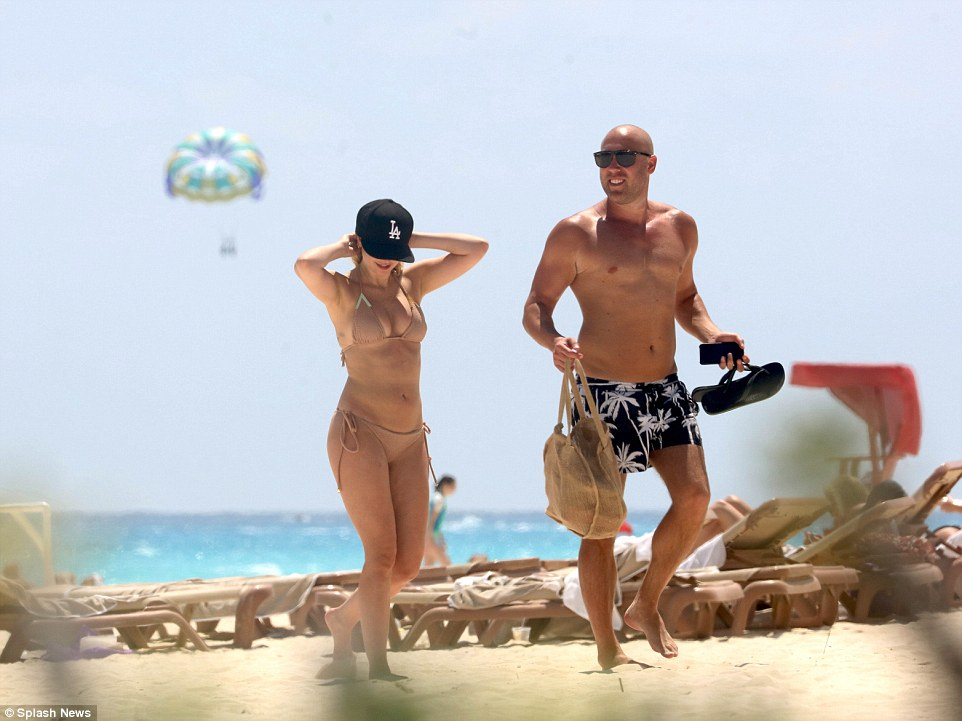Ready to tan: The reality star's companion carried his flip-flops and beach bag