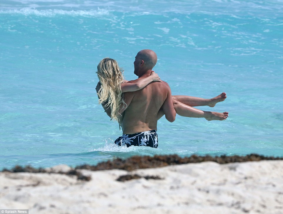 One way to stay dry! Her companion could barely keep his hands to himself, as he carried the Miami-native into the cobalt waters