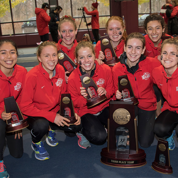 Women's Cross Country poses with trophies