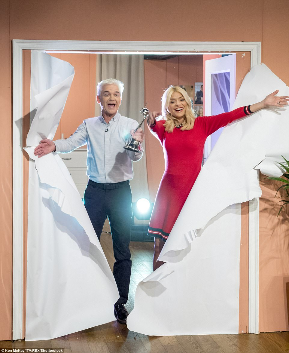 Nice gong: Phillip and Holly made quite the entrance as they burst through a paper wall into the studio