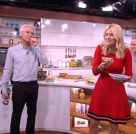 Wolfing it down: Phil appeared rather shocked as Holly gobbled it up live on air as he certainly wasn't at a point where he could consider eating yet
