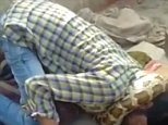 The man could be seen in visible distress as he slumped to the floor with the python wrapped around his neck