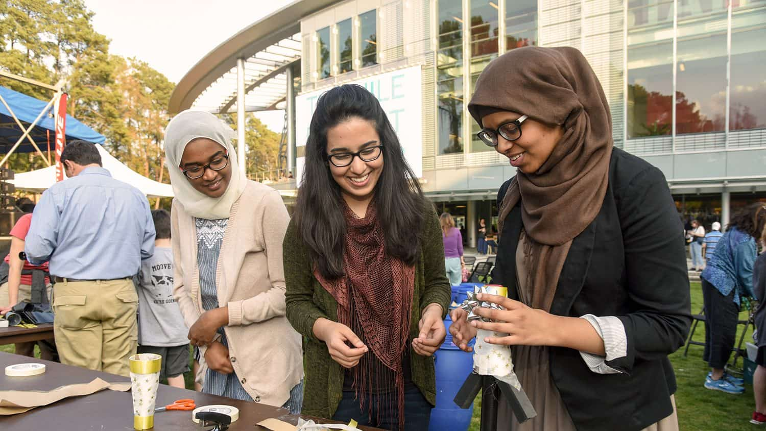 Three women work together at the Nile Project event outside Talley Student Union.