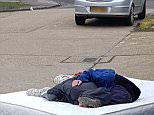 The picture, taken over the weekend, shows two people asleep on the floor in the middle of the road in South Ockendon, Essex