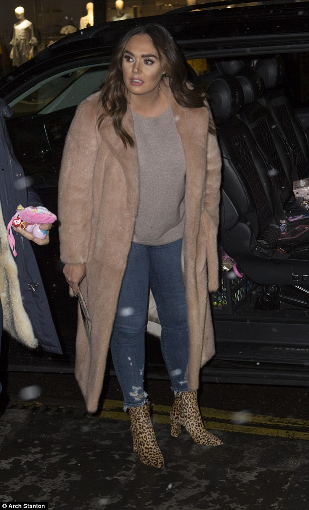 Fashionista: The socialite teamed the statement outerwear with a chunky knit, ripped skinny jeans and a pair of towering leopard print ankle boots which boosted her height