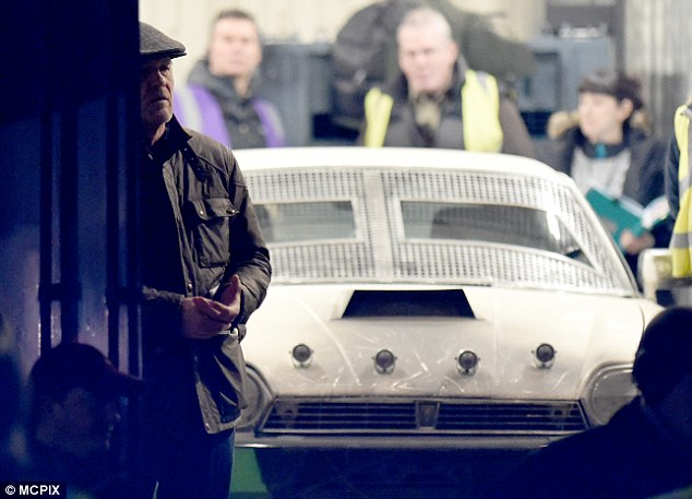 Hats on: Sean's character kept a low-profile alongside a white sports car while he covered his hair with a flat cap