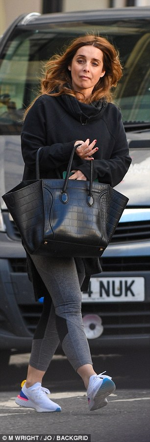 Call me: Louise clutched on to her mobile phone as she sauntered down the street