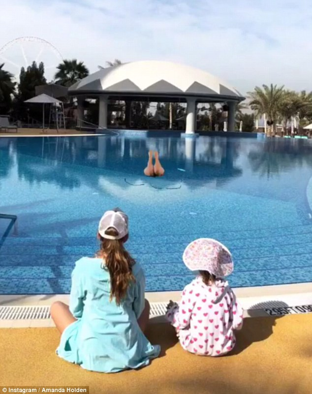 Blue lagoon: The same day, Amanda shared a sweet photo of daughters 6 year-old Hollie and Lexie, 12, hanging out beside the exotic pool in their sun hats and colourful robes