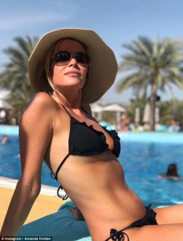 Beach babe: Amanda has shared a number of sizzling snaps from her getaway so far - having stunned fans with her impressive figure in a skimpy black bikini on Tuesday