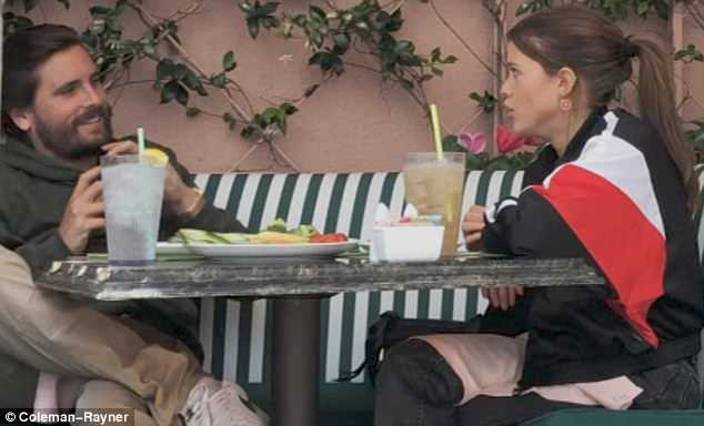Lunch date: The two sat at a green booth with a striped back and looked at ease opposite one another