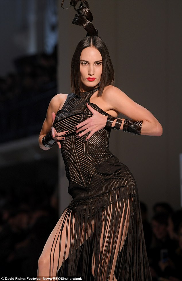 Saucy: Another model saucily grappled with her assets as she modelled a laser-cut fringed number