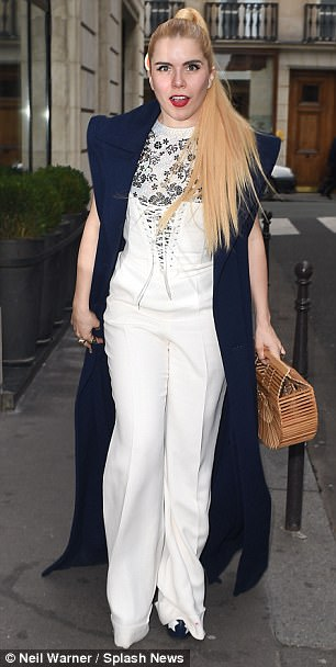Flare for fashion:The 36-year-old showed off her svelte figure in the white one-piece, which cinched in at her slim waist with its lace-up detailing before extending into flared trousers