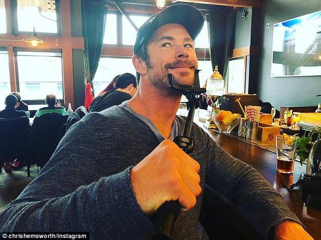 'This new selfie stick is so cool':Chris then showed off his playful side as he posed with his selfie stick tucked around his chin during a break from surfing
