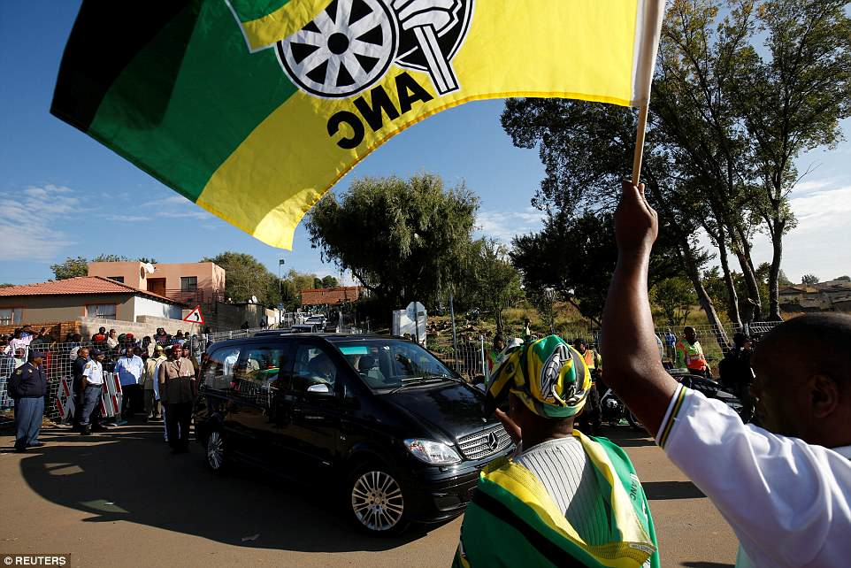 People pay their respects as the coffin of Winnie Mandela is driven from her home to Orlando Stadium during her funeral in Soweto
