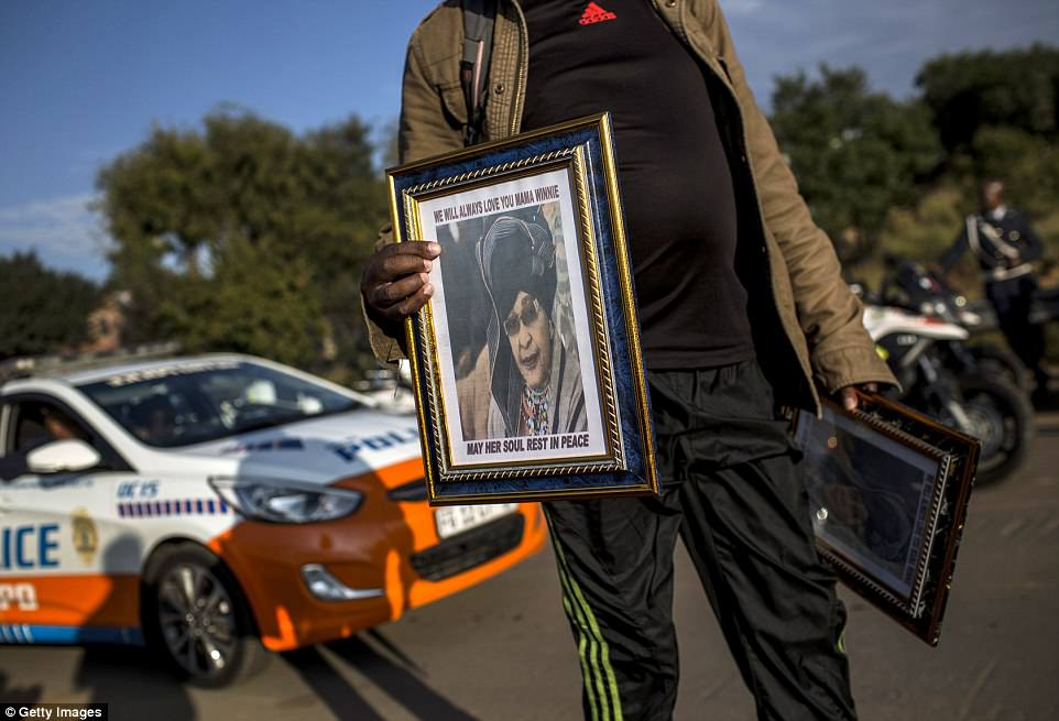 A man walks the street in front of Winnie Mandela's house with posters of her prior to the funeral at Orlando Stadium in Soweto