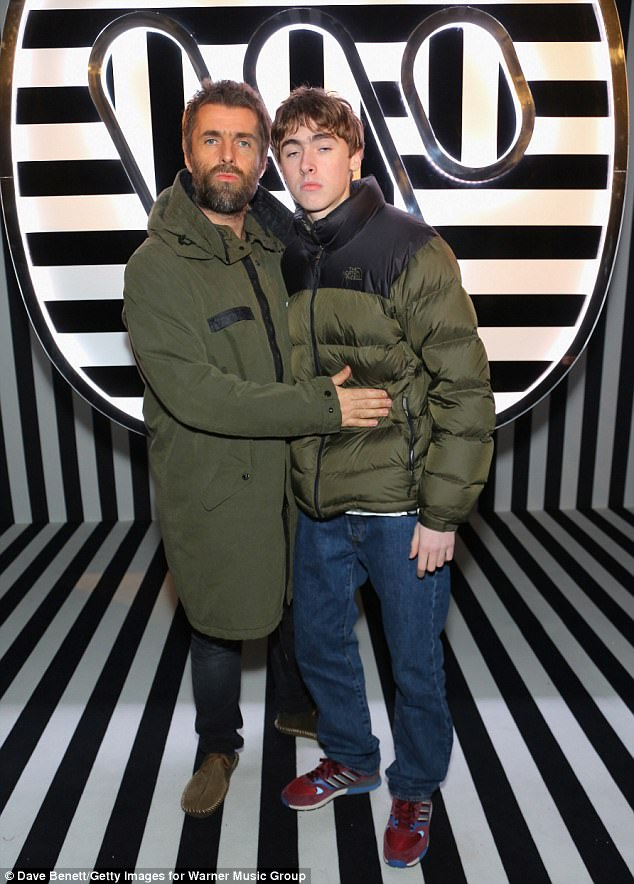 Family outing: Liam Gallagher, 45, struck a matching snarly pose with look-a-like son Gene, 16, at BRITs after-party... as they were  joined by Oasis singer's girlfriend Debbie Gwyther, 34