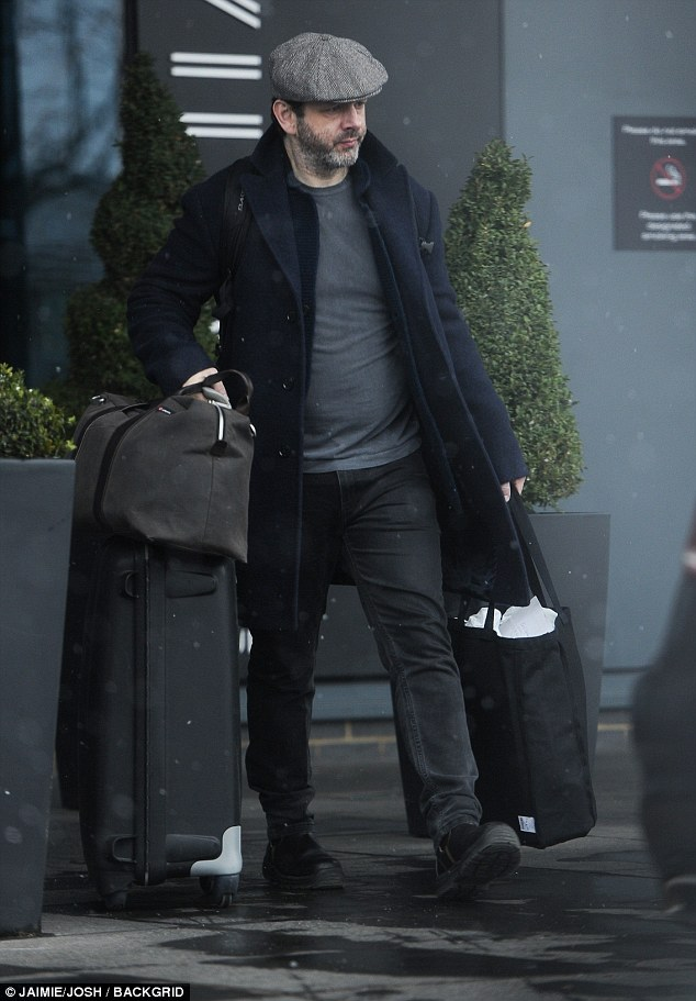 Flying solo: The actor, wrapped up in a navy pea coat as he braced the snowy weather and made his way to an awaiting taxi laden with luggage
