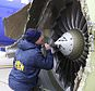 """In this Tuesday, April 17, 2018 photo, a National Transportation Safety Board investigator examines damage to the engine of the Southwest Airlines plane that made an emergency landing at Philadelphia International Airport in Philadelphia. A preliminary examination of the blown jet engine of the Southwest Airlines plane that set off a terrifying chain of events and left a businesswoman hanging half outside a shattered window showed evidence of """"metal fatigue,"""" according to the National Transportation Safety Board. (NTSB via AP)"""