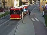 The two girls were walking down the street in Poland as the bus goes past