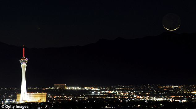 The comet PanSTARRS, above and to the right, passes over the Stratosphere Casino Hotel, Las Vegas: Observers in southern U.S. states have already been able to see it for several days