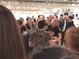 The Chinese man was seen held in a headlock by security personnel and dragged away