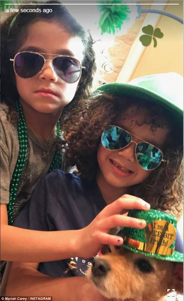 Getting in the spirit: The twins wore snazzy green aviators as they popped a glittery green hat on their pet dog