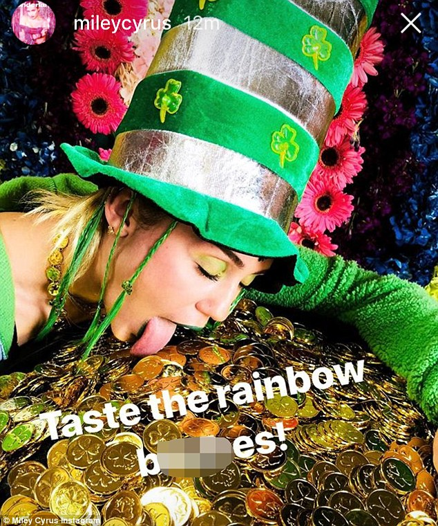 Yummy?Malibu singer Miley Cyrus was seen licking a pot of gold coins with a green and silver hat on