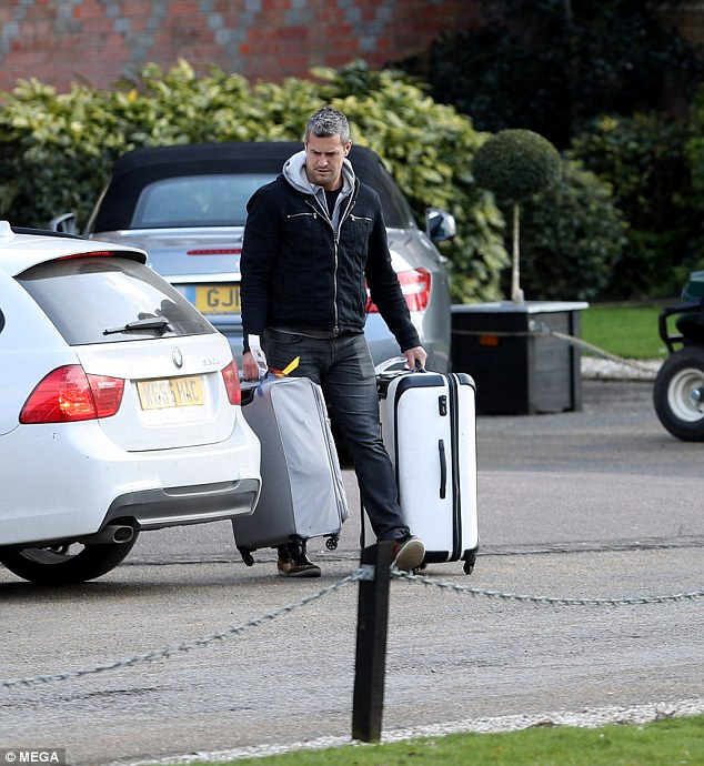 Double fisting: The television presenter showed he had serious muscle as he carried two luggages
