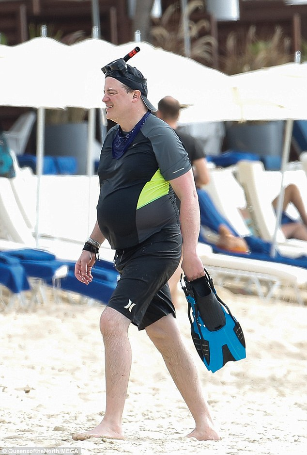 All rigged up: The Bedazzled actor carried a pair of blue and black flippers and had snorkel gear on his head over his black cap
