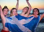 Students from the University of St Andrews protect their modesty with a Scottish flag after jumping into the North Sea today