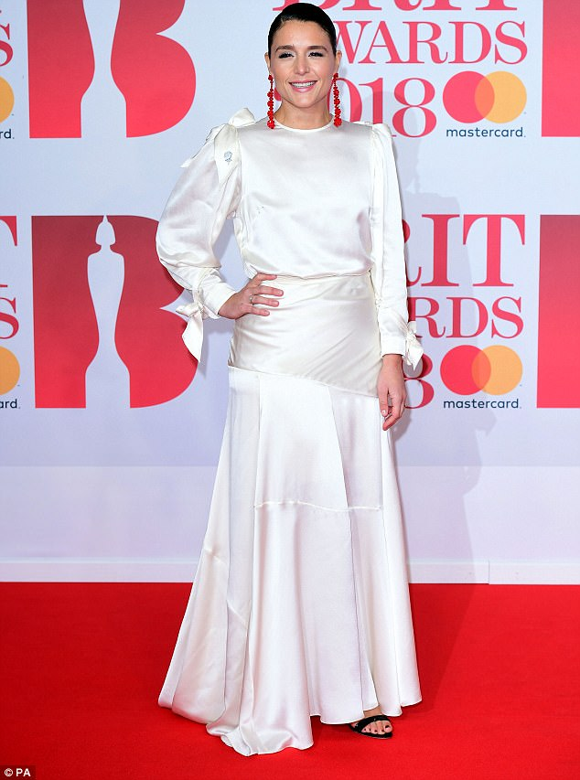Wonder in white:The singer, 33, looked happy and relaxed as she cosied up to her long-term love, wearing a beautiful white long-sleeve gown, adorned with delicate bow features