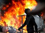Paris is burning: A car and a motorcycle have been set alight outside a Renault automobile garage during the protest