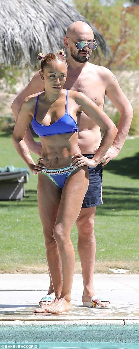 Sizzling hot! Mel Bshowcased her perky assets and washboard abs as she slipped into a plunging purple bikini during her  Desert Hot Springs retreat in California with her best pal Gary Madatyan on Friday afternoon