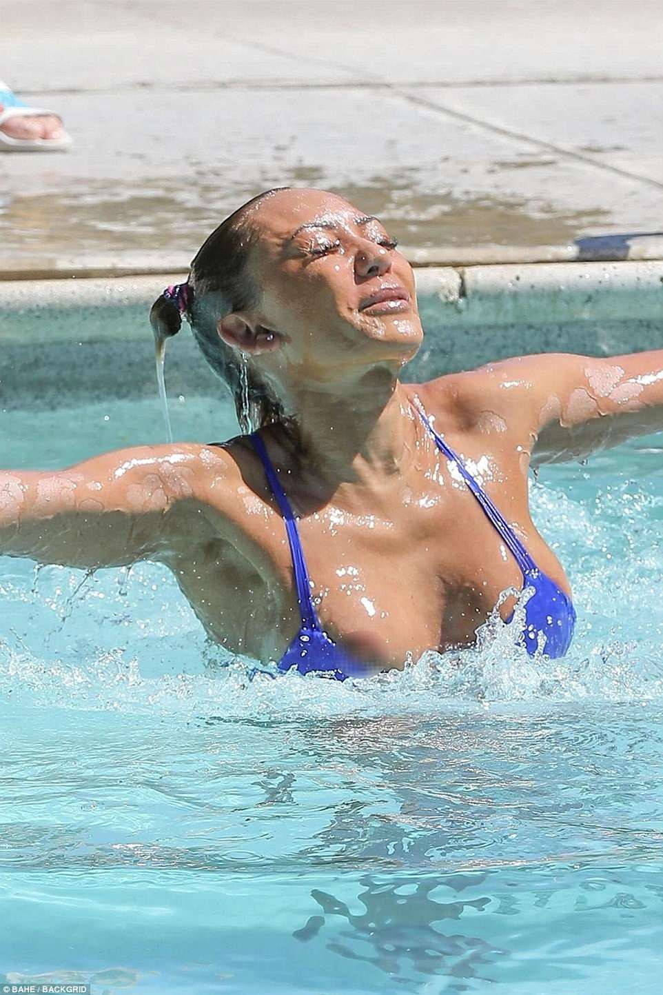 Oops! The Spice Girls star, 42, flashed a little too much as she spilled out her bikini top while taking a refreshing dip in a pool