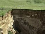 This image made from the May 2, 2018 video shows huge sinkhole on farm in Rotorua, New Zealand.  A spectacular sinkhole the length of two football fields and the depth of a six-story building has opened up on a New Zealand farm. A worker stumbled upon the chasm before dawn this week when he was rounding up cows for milking on the farm near the North Island town of Rotorua. It appeared after several days of heavy rainfall. (Newshub via AP Video)