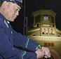 """An unidentified uniformed man adjusts his wristwatch in front of a clock of the Pyongyang Station in Pyongyang, North Korea, early Saturday, May 5, 2018. North Korea readjusted its time zone to match South Korea's on Saturday and described the change as an early step toward making the longtime rivals """"become one"""" following a landmark summit. The portraits seen in the background are the late leaders, Kim Il Sung, left, and Kim Jong Il. (Kyodo News via AP)/Kyodo News via AP)"""
