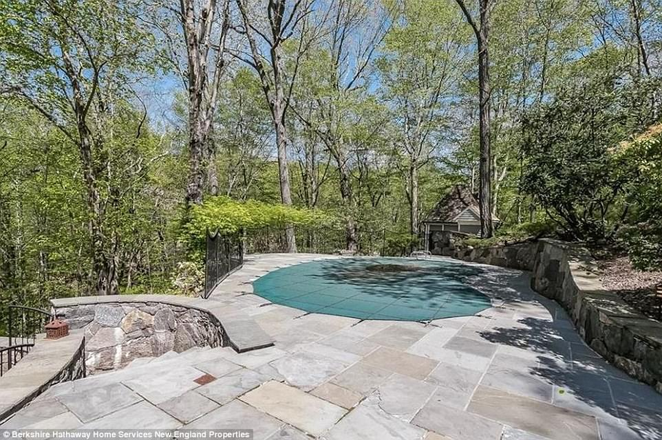 Water view: A partial wrap-around stone terrace overlooks the back yard and kidney-shaped swimming pool