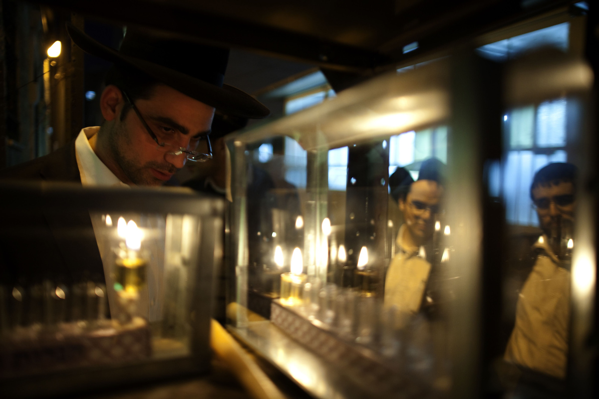 A Jewish man lights candles on the first night of the Jewish holiday of Hanukkah in the Haredi neighbourhood of Mea Shearim i