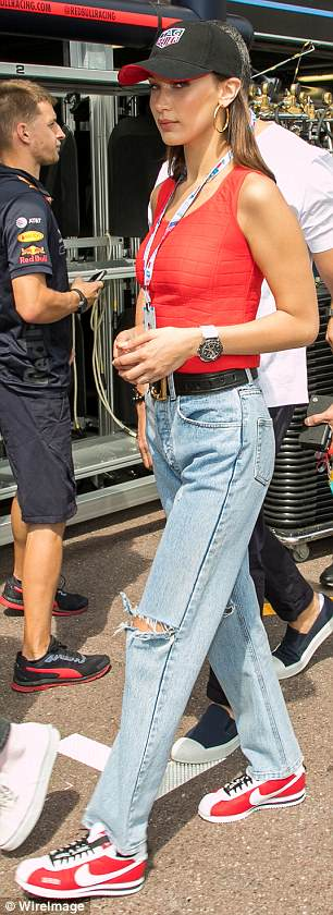 Stylish:Looking every inch the fashion maven, the model tied in her outfit with a pair of light-wash jeans, which were slashed at her knees for a trendy ripped effect