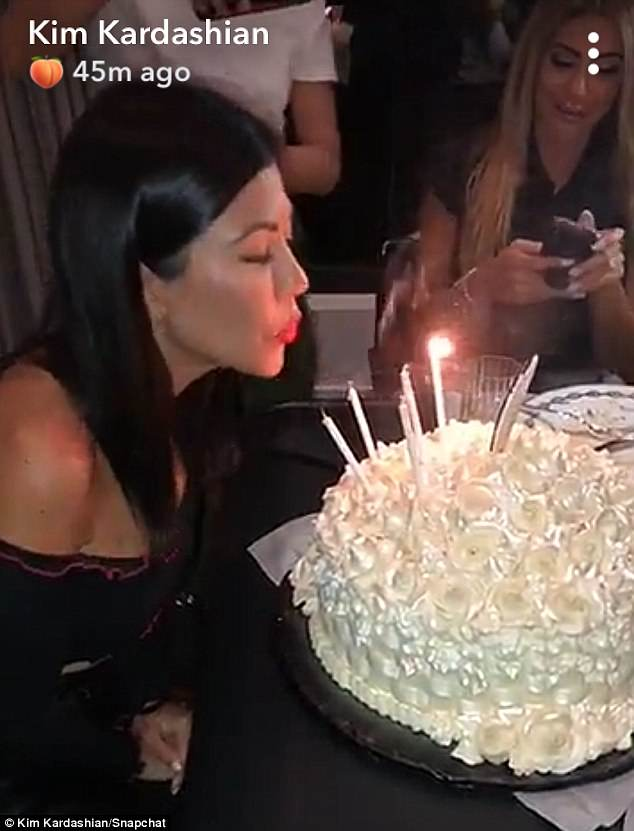 Kourtney is then presented with a cake, and she proceeds to successfully blow out all the candles before taking some selfies with Kim