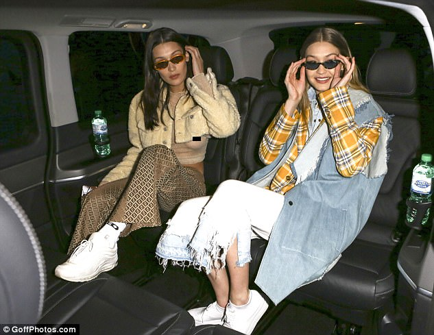Sartorial sister act: Leaving the Alberta Ferretti show with elder sister Gigi, 22, the supermodel flashed her bust whilst sorting out her hair