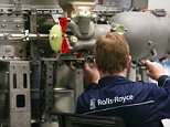 An employee works on a Trent aircraft engine on the production line at the Rolls-Royce Holdings Plc factory in Derby where cuts are expected to be made - although it is middle management and office staff who are likely to take the hit, it has been reported