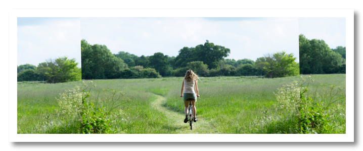 Young woman biking through countryside meadow.