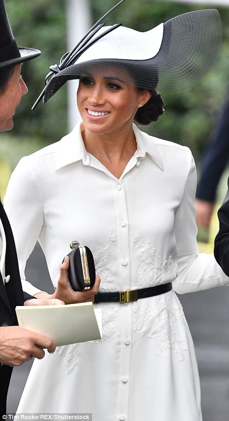 Meghan accessorised her dress with a black clutch bag