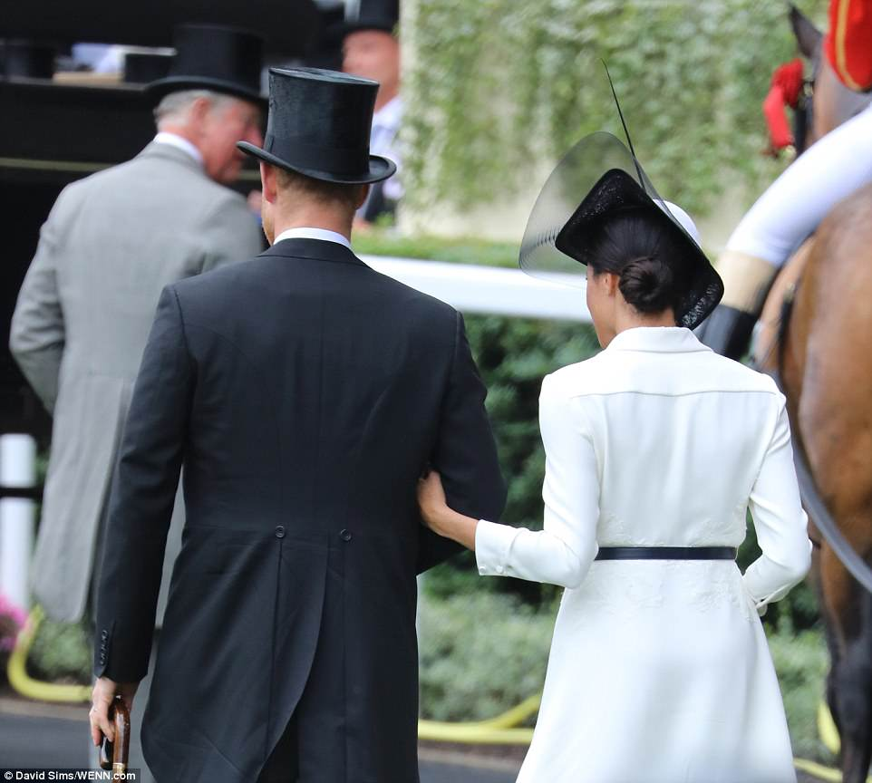 Harry and Meghan were seen walking around the Berkshire racecourse arm in arm, during their first joint appearance today